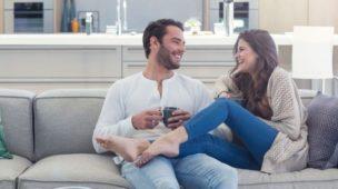 Casal descontraído conversando no sofa